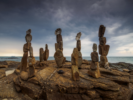 View of a stony shore of the sea with stone pyramids on it under the heavy stormy sky Stock Photo