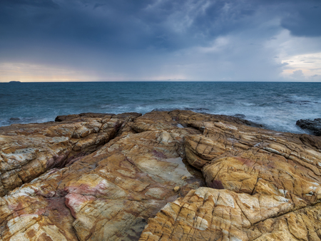 View of a stony shore of the sea under the heavy stormy sky