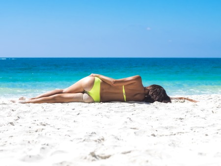 Sun-tanned young girl in yellow bikini lying on the sand shore of the sea. View from the back