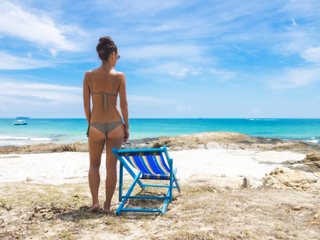 Sun-tanned young girl in gray bikini standing on the stony shore of the sea near the deck chair. View from the back