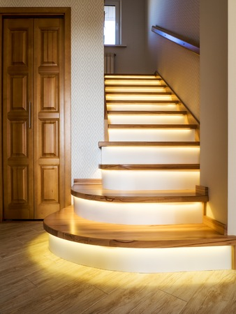 Home interior. Spiral staircase with wooden steps and illumination Stock Photo