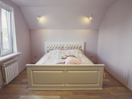 Cozy bedroom with double bed. Pastel toned