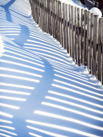 Wavy shadow from a wooden fence on snowdrifts