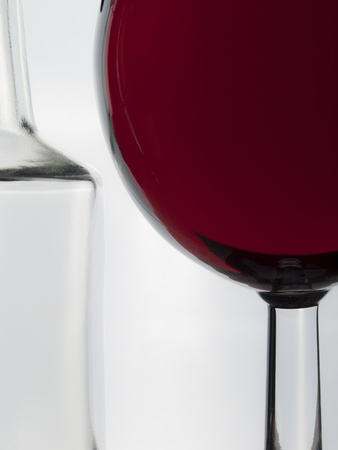 Glass of wine and empty bottle on the white background