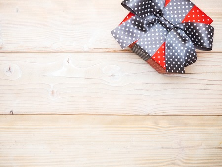 Gift box in glittery paper with bow on wooden board. Holidays concept Stock Photo