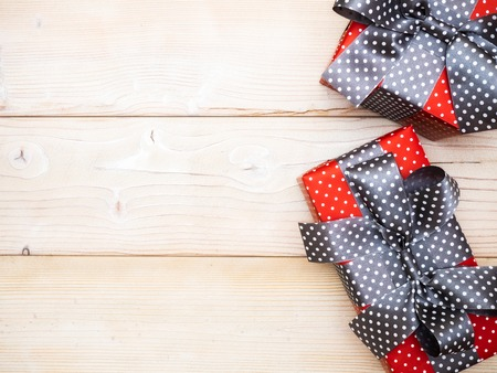 Gift boxes with brown ribbons on wooden board. Holidays concept