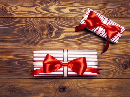 Gift boxes with red-white ribbons on wooden board. Holidays concept
