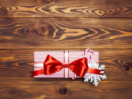 Birthday present with red-white satin tape on wooden board. Holidays concept