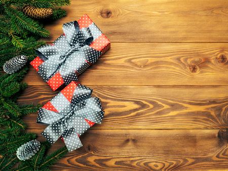 Christmas composition. Fir branches with cones along with gift boxes on the wooden background. Top view. Holiday concept Stock Photo