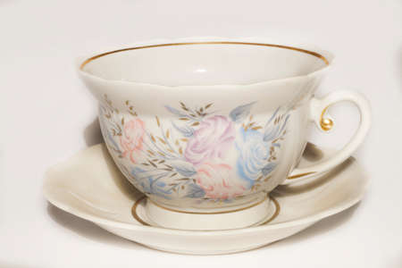 the gilding: Antique porcelain saucer and cup with a pattern and gilding