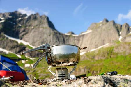 Un brûleur à gaz portatif sur un rocher à Lofoten, en Norvège, en face de Nonstinden et Sautinden. Banque d'images - 79886922