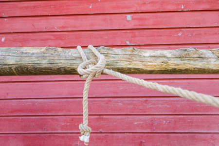 Rope tied in a knot on a hitching post in front of a red barn wall