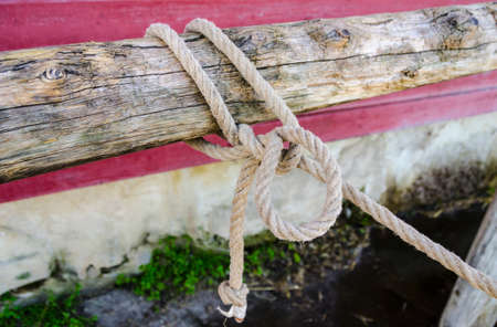 Rope tied on a worn hitching post Stock Photo