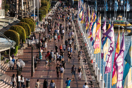 darling: Sydney, Australia - Mar 26, 2016: Aerial view of crowd of people in Darling Harbour. Tourists and locals walking along the promenade on Cockle Bay Wharf on sunny day Editorial