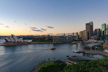 Sydney Circular Quay, CBD skyscrapers and ferries on sunrise. Urban landscape view from above. Sydney, Australia