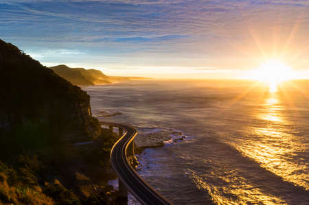 Sea cliff bridge along Australian Pacific ocean coast on sunrise. Sun rising out of sea with sun rays and sun flare visible. NSW, Australia