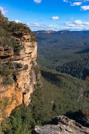 Rough cliff faces of Wentworth Falls track with unidentifiable people on path in a distance. Blue Mountains National Park, NSW, Australia