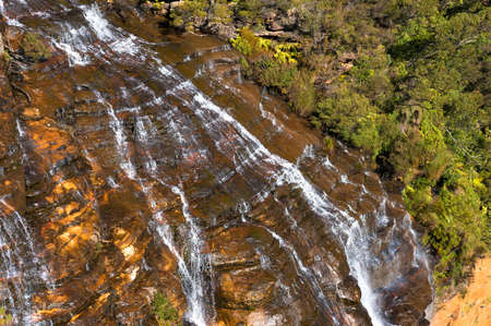 Close up of waterfall with water flowing over rock surface. Wentworth Falls in Blue Mountains National Park. New South Wales, Australia