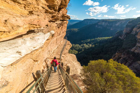 Mountain landscape with a woman hiking, going downstairs mountain track. Wentworth Falls, Blue Mountains National Park, Australia