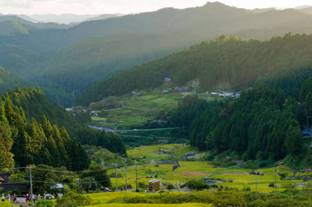 atmospheric: Sunset view over Japanese countryside with mountains and rice fields. Sun rays creating long shadows over mountain rural landscape. Yotsuya, Aichi prefecture, Japan