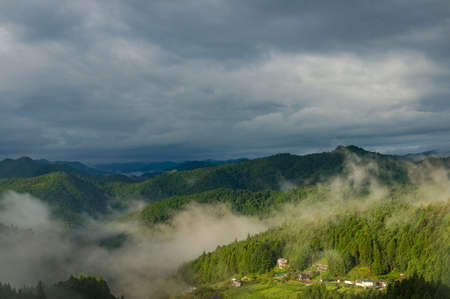 Mountain forest village with layers of fog against dramatic sky on the background. Yotsuya no Semmaida, Japan Stock Photo