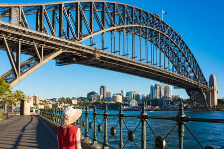 Woman in bright top and hat against Sydney Harbour Bridge on the background. Tourist destination concept