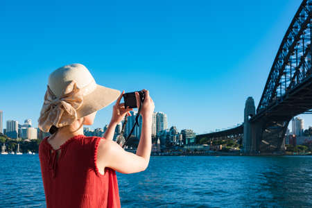 Woman in red top and summer hat taking pictures of Sydney Harbour Bridge with view of Milsons point on the background 写真素材