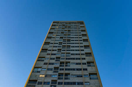 postwar: Tall building with windows against blue sky on the background. Oppressive architecture design in post-war international style