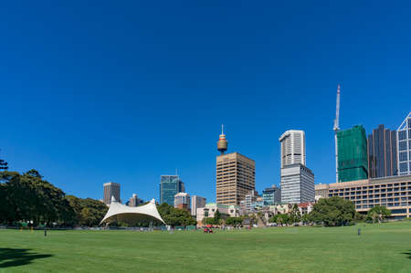 public space: Sydney, Australia - November 24, 2016: Sydney Domain, public space with tent stage and Sydney CBD skyline on the background