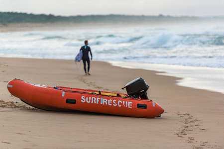 Life saver boat on sandy ocean sore with unidentifiable male surfer walking in the distance