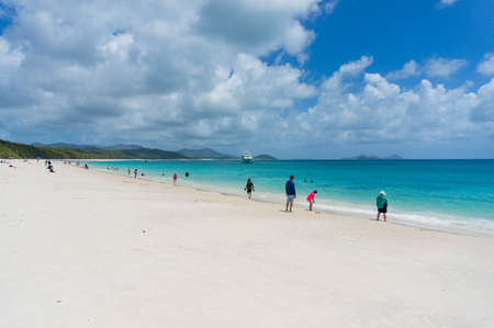 Whitehaven beach with people having fun on famous silica white sand and turquoise blue waters. Queensland, Australia Stock Photo