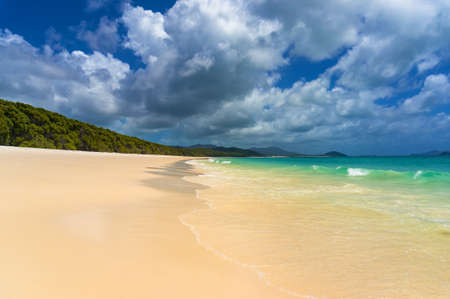 Beautiful tropical beach with piqturesque cloudscape. Summer holiday, vacation background. Whitehaven beach on Whitsunday island, Queensland, Australia