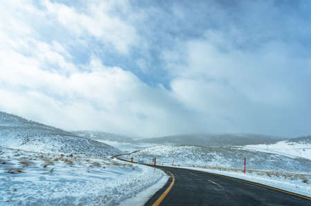 Australian winter landscape of snow covered filends and ice-covered road. Snowy Mountains, Australia