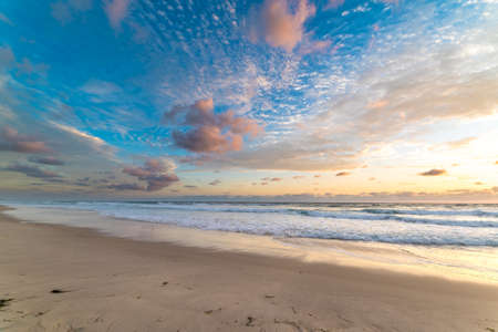 surfers paradise: Beautiful beach landscape with picturesque sunrise sky and soft waves over sand Stock Photo