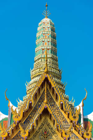 Beautiful Asian style architecture. Lavishly decorated roof and stupa of building in Grand Palace. Bangkok, Thailand