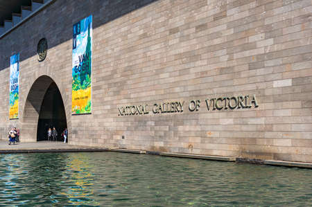 southbank: Melbourne, Australia - April 18, 2017: National Gallery of Victoria entrance door with colorful banners of new exhibition and water pool on the foreground