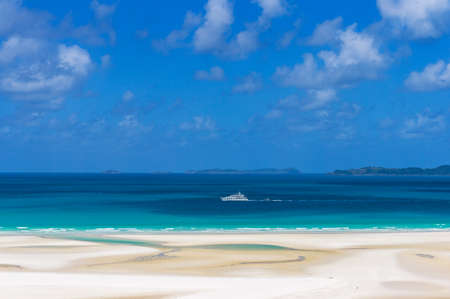 whitehaven beach: White cruise liner on turquoise blue waters of Coral sea on sunny day. Summertime vacation, holiday background. Whitsundays, Whitehaven beach. Queensland, Australia