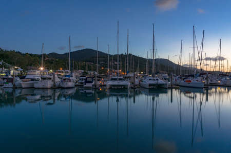 Yachts, boats and catamarans on berth in bay at night. Airlie beach, Australia Stock Photo