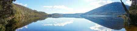 Panorama of beautiful mountain range landscape reflected in smooth water surface of lake on clear day Stock Photo