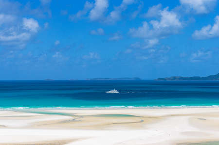 whitehaven beach: White cruise ship, boat on turquoise blue waters of Coral sea on sunny day. Summer vacation, holiday background. Whitsundays, Whitehaven beach. Queensland, Australia