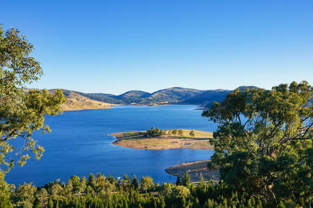 Aerial view of outback landscape with blue lake surrounded by hills, mountains and green trees of eucalyptus forest. Wyangala, NSW, Australia Stock Photo