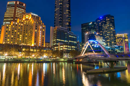 Melbourne, Australia - April 17, 2017: Beautiful cityscape at night with bridge across river Beautiful Melbourne Southbank cityscape at night with Evan Walker pedestrian bridge across Yarra river