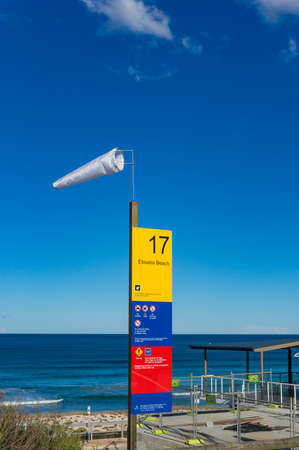 Cronulla, Australia - May 24, 2017: Windsock and information board at Elouera beach in Cronulla suburb. High wind weather on sunny weather