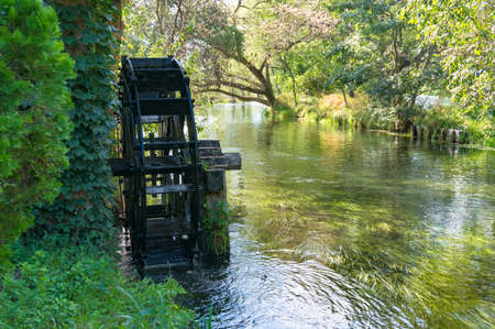 water mill: Water mill wheel on river. Water power and renewable energy traditional machinery