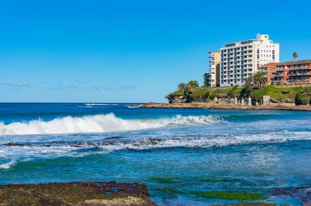estate: Beautiful waves and waterfront buildings on sunny day. Cronulla, Australia