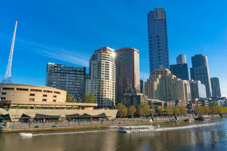 west river: Melbourne, Australia - April 4, 2017: Beautiful Melbourne Southbank skyline with cruise boats on Yarra river and sun reflected on building window on bright sunny day