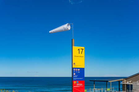 high winds: Cronulla, Australia - May 24, 2017: Windsock and information board at Elouera beach in Cronulla suburb. High winds on sunny weather