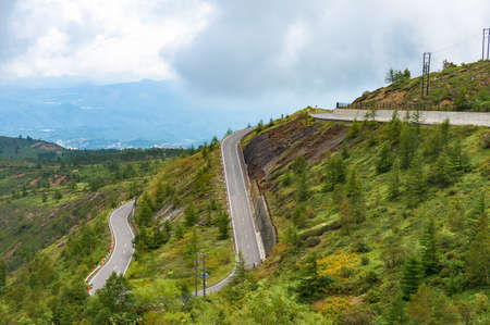 Windy mountain road. Bending road over mountain slope. Infrastructure and transportation in rural Japan