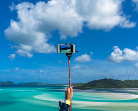 whitehaven beach: Person taking photo on beautiful tropical lagoon on smartphone