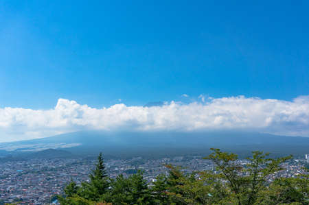 Aerial view of Fujiyoshida town and Mount Fuji peaking over clouds on sunny day. Yamanashi prefecture, Japan Stock Photo